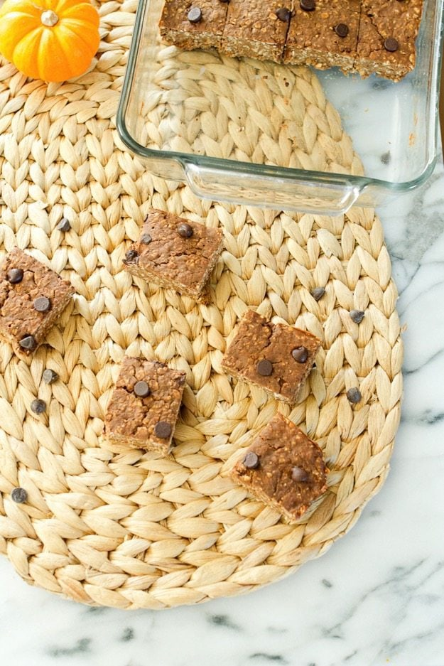 Pumpkin bars cut in squares scattered on the woven place setting. Clear baking dish with some bars in the upper right corner of the picture.