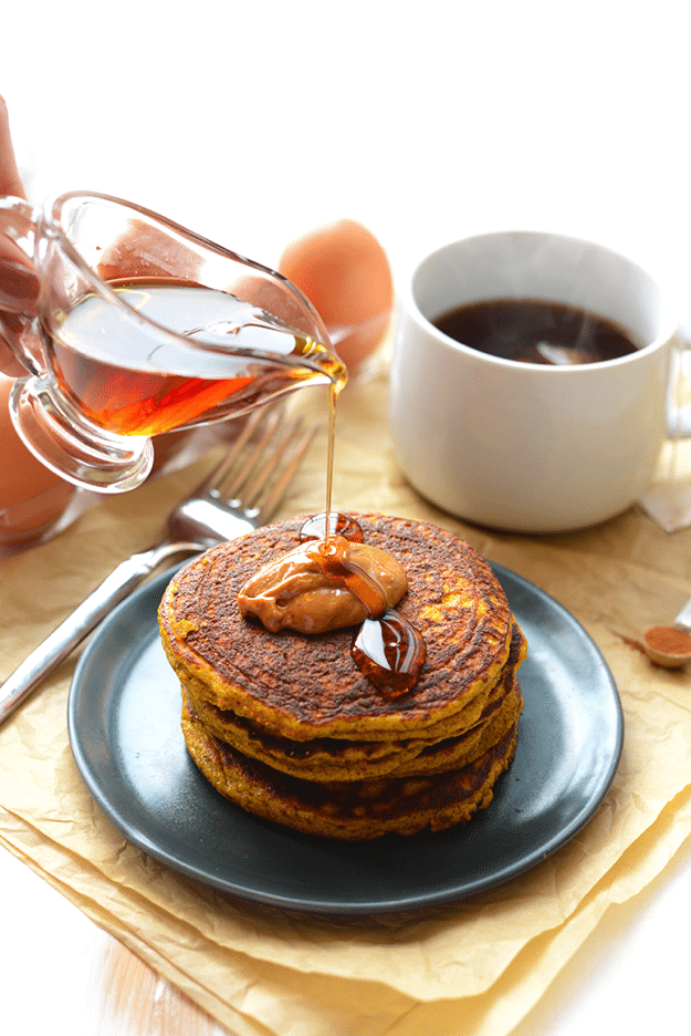 Paleo pumpkin pancakes stacked on a dark plate with a hand pouring maple syrup over the top. White mug of tea in the background.