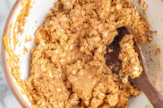 Ingredients for pumpkin protein bars mixed together with a wooden spoon.
