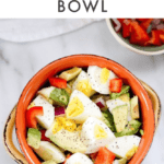 One bowl with chopped hardboiled eggs, avocado, and vegetables, another bowl with chopped peppers and onions, hardboiled egg on the side.