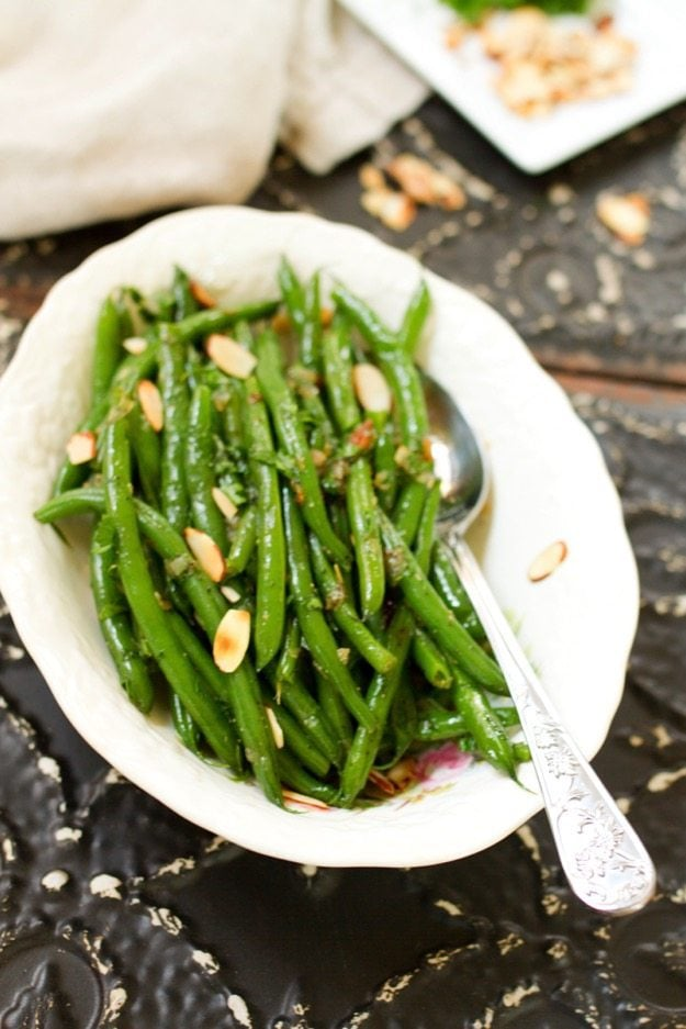 Add some green to your holiday table with this flavorful recipe for tender crisp green beans tossed with caramelized shallots, toasted almonds and fresh parsley. #vegan #glutenfree #paleo