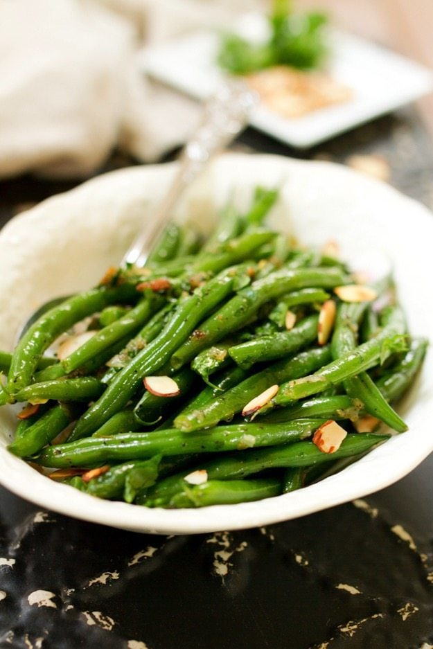 Add some green to your holiday table with this flavorful recipe for tender crisp green beans tossed with caramelized shallots, toasted almonds and fresh parsley. Vegan, gluten-free and paleo.