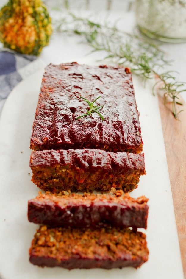 Lentil Loaf with a Maple Glaze sitting on a white platter. Three slices cut.