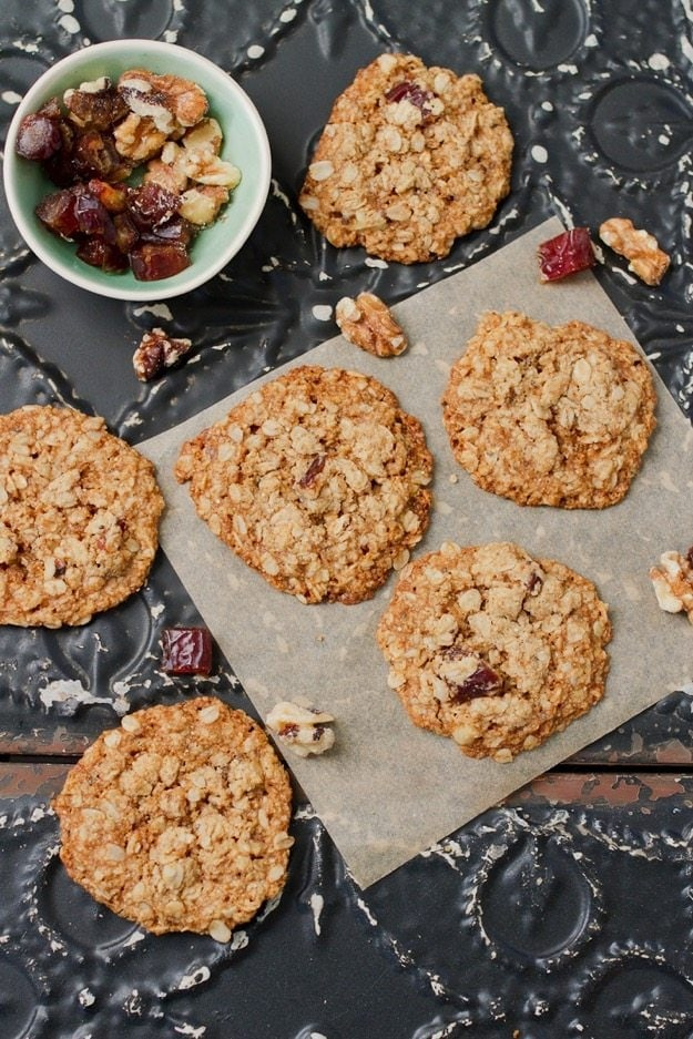 Seven Oatmeal Date Cookies on a table with nuts and dates scattered around the cookies.