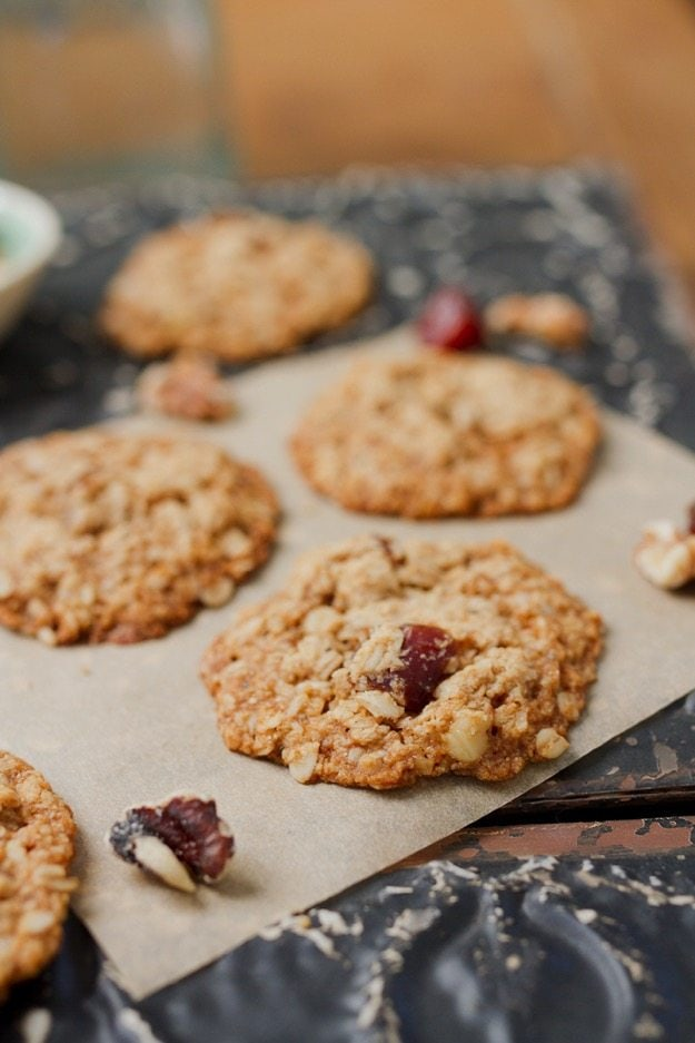 Oatmeal Date Cookie in the front of the frame with more cookies, nuts, and dates in the background.