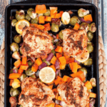 Sheet pan of roasted chicken, butternut squash, Brussels, onion, and lemon.