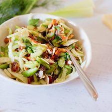 A bowl of fennel and celery salad in a white bowl. A spoon is sticking out of the bowl.