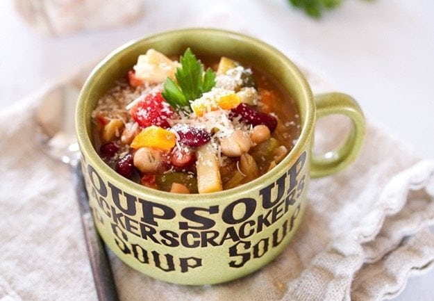 Minestrone soup in a green mug sitting on a linen towel.
