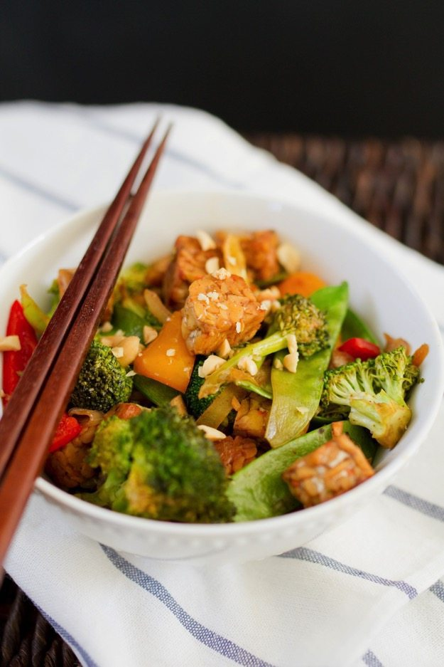Kung Pao Tempeh in a bowl with stir fried veggies and chop sticks.