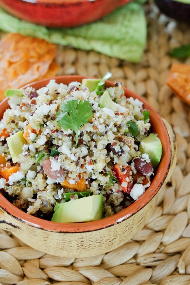 Southwestern quinoa salad sits in a bowl that rests on a straw mat. Avocado and cilantro garnish the dish.