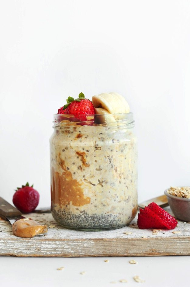 Peanut Butter Overnight Oats in a glass jar topped with strawberries and sliced bananas.