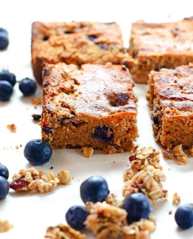 Sliced berry carrot cake bars on a white counter with granola crumbles and blueberry.