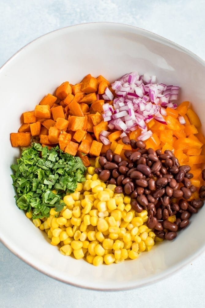Ingredients for a southwestern quinoa salad in a bowl before being mixed: sweet potato, onion, peppers, black beans, corn, and cilantro.