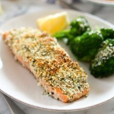 A filet of hemp and pecorino crusted salmon on a plate with broccoli and a lemon wedge out of focus on the plate.