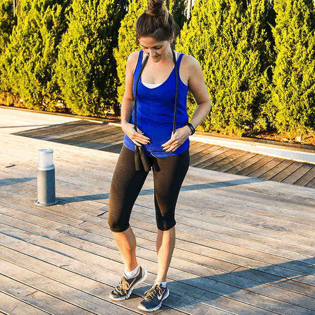 Girl in black workout pants and blue tank top holding a black jump rope outside.