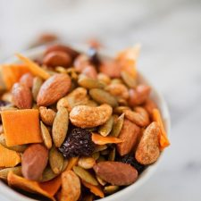 A white bowl filled with dried mango, nuts, seeds, and raisins, covered in curry spices.