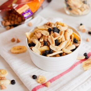 A bowl filled with peanuts, peanut butter chips, dried blueberries, and banana chips. Bag of peanut butter chips in the background.