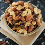 Pizza Trail Mix in a bowl, on top of a folded cloth napkin. Trail mix make from mixed nuts and dried tomatoes with seasoning.