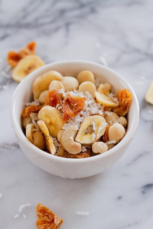 Take a trip to the tropics with this island-inspired tropical trail mix with cashews, macadamia nuts, banana chips, dried pineapple and coconut.