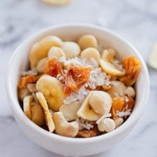 White bowl on white marble, filled with tropical trail mix with cashews, macadamia nuts, banana chips, dried pineapple and coconut.