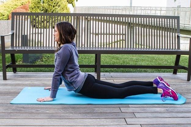 Girl on yoga mat doing a cobra/up dog stretch.