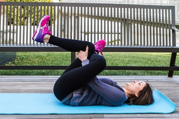 Girl on yoga mat doing a glute stretch.