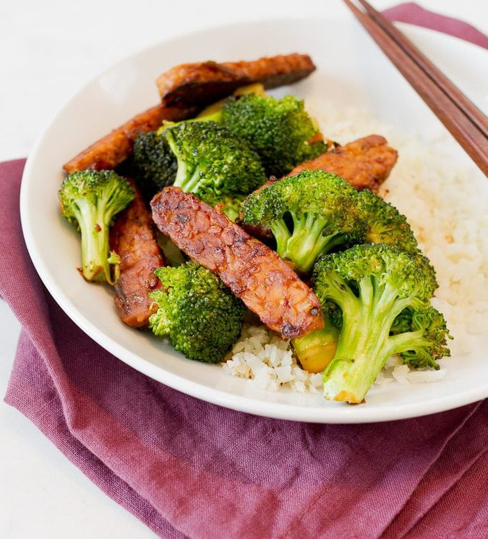 Tempeh and broccoli stir-fry in a bowl with cauliflower rice.