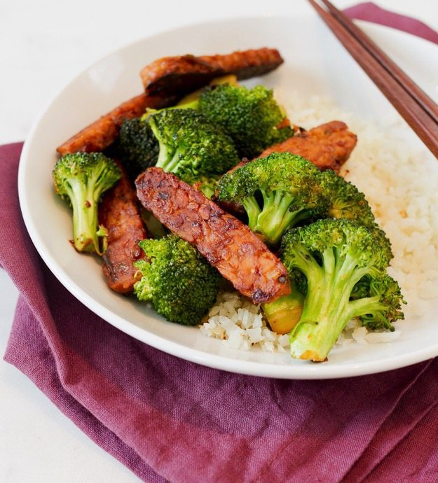 Garlic Teriyaki Tempeh and Broccoli in a white bowl, sitting on a maroon napkin.