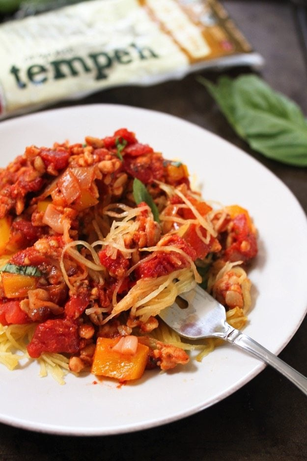 This plant-based bolognese sauce with ground tempeh is served over spaghetti squash for a hearty meal that's easy to make, packed with protein and super healthy!