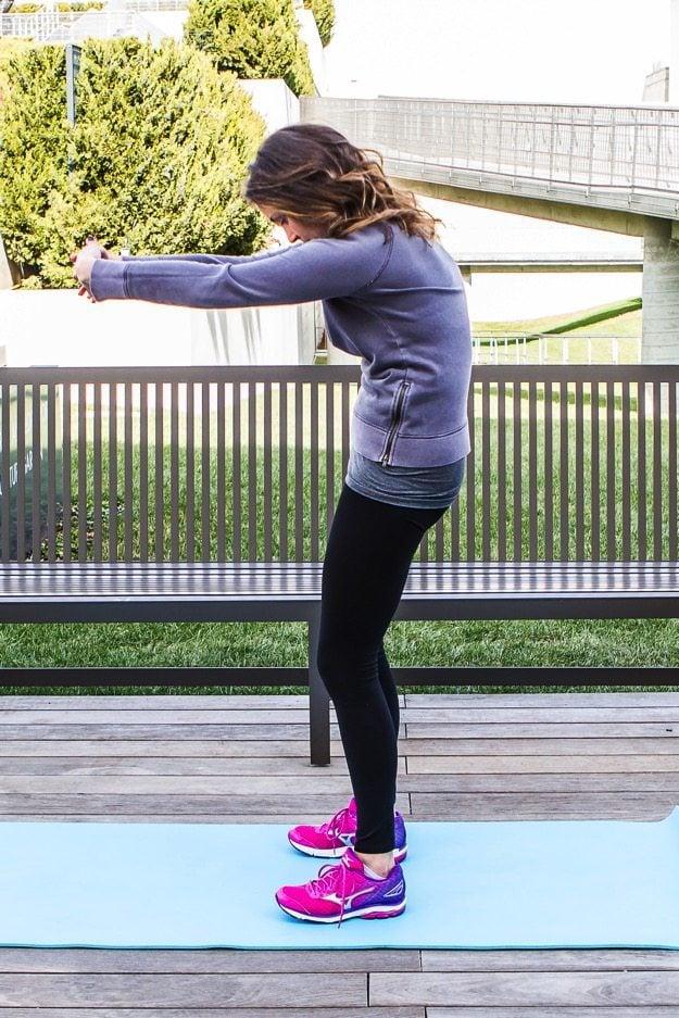 Girl on yoga mat doing an upper back stretch.
