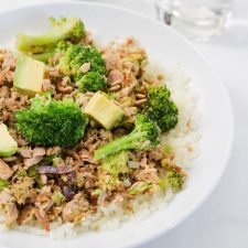 A bowl with broccoli avocado tuna served over rice.