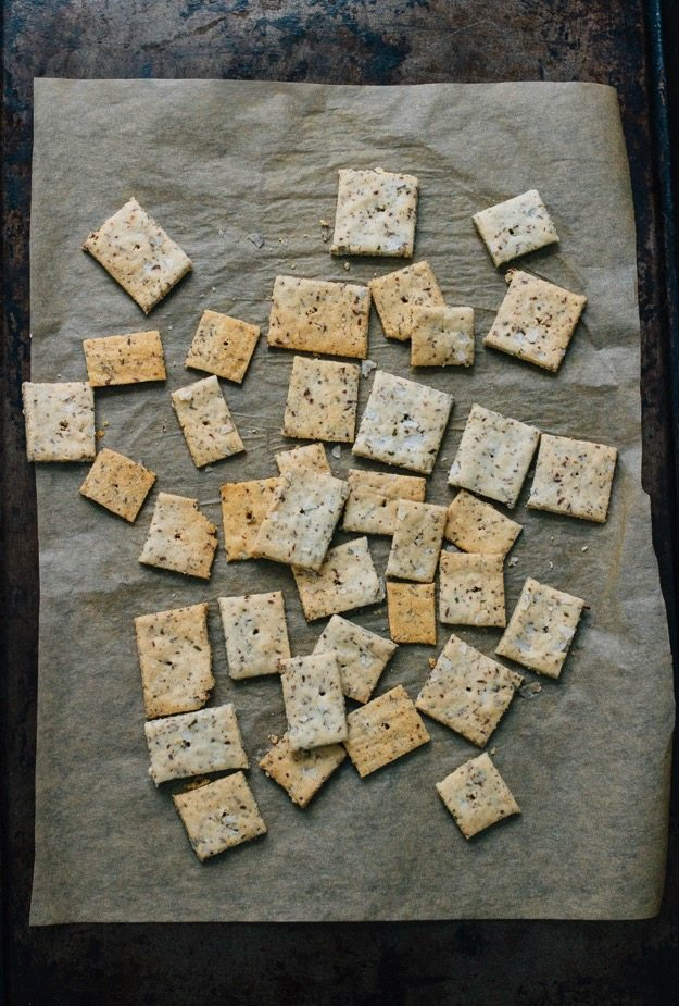 Overhead shot of homemade almond crackers on parchment paper and baking sheet.