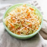 Cabbage and carrot slaw in a mint green bowl on a neutral cloth.