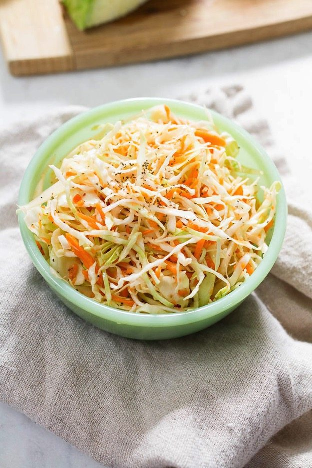 Light green bowl with coleslaw sitting on neutral towel.