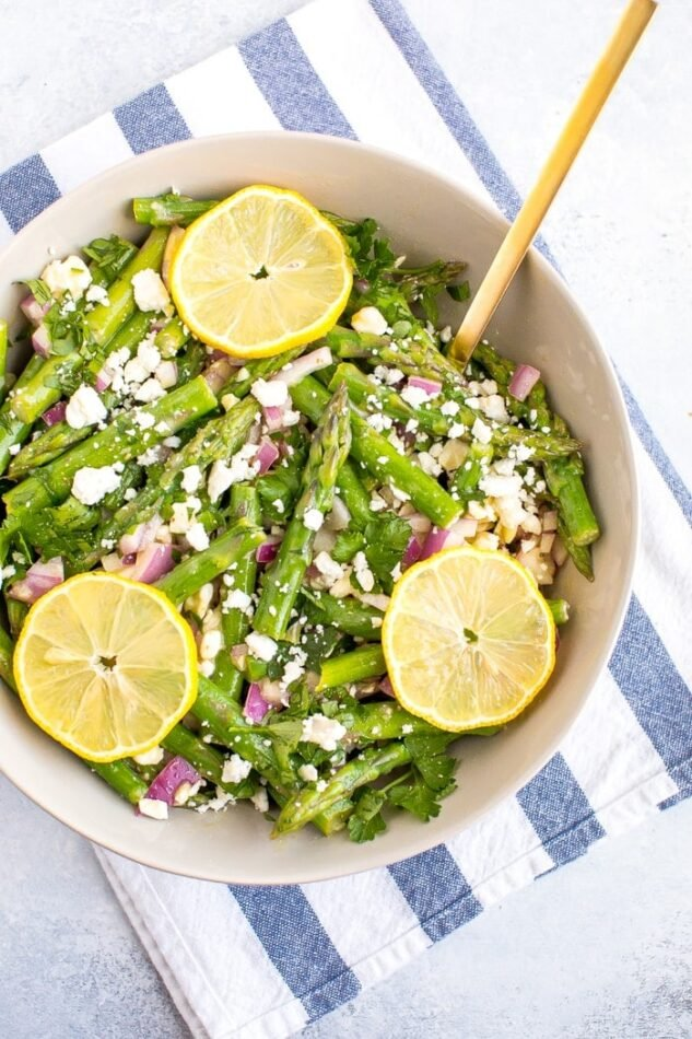 Asparagus feta salad in a large bowl with a gold spoon and lemon slices on top.