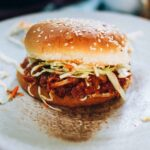Hearts of palm bbq sandwich with slaw on a sesame seed bun on a white plate.