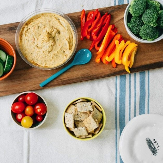 Overhead shot of cutting board with hummus, chopped veggies, and homemade almond crackers.