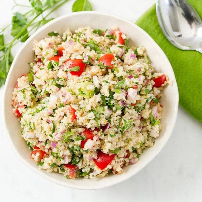 Bowl filled with quinoa tabbouleh-- quinoa, parsley, tomatoes and onions. Bowl next to a cloth napkin, spoon, and herbs.