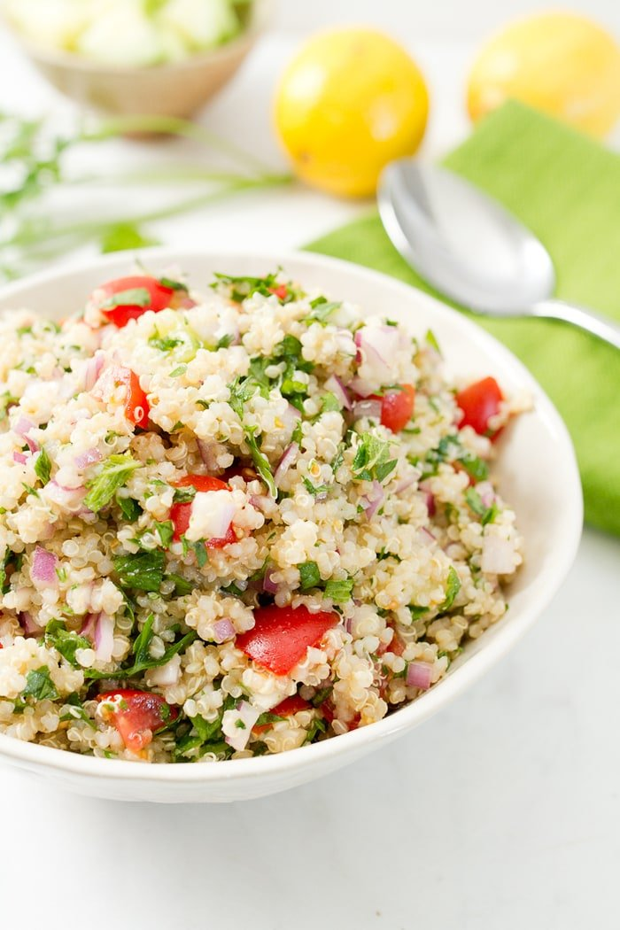 Bowl filled with quinoa tabbouleh-- quinoa, parsley, tomatoes and onions. Bowl next to a cloth napkin, spoon, lemon and herbs.