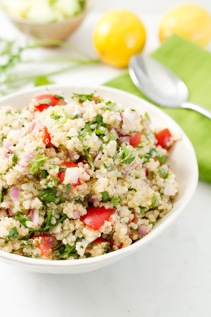 Quinoa tabbouleh in a white bowl with a place setting on a table.