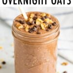 Mason jar filled with brownie batter overnight oats and topped with walnuts and dark chocolate chips.