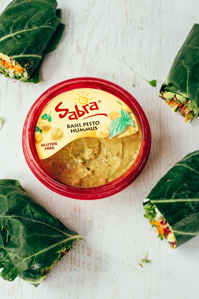 Sabra basil pesto hummus container sitting on a white wood counter in the center of the frame. Four collard green wraps around the edge.
