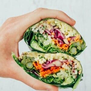 Hand holding two halves of veggie packed hummus collard wraps.