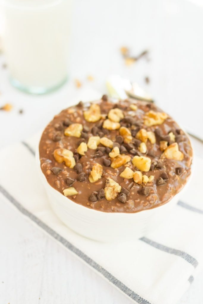 Bowl of brownie batter overnight oats, topped with chocolate chips and walnuts.