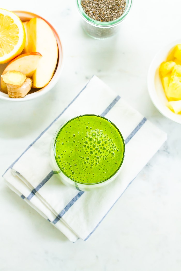 Glass with a green pineapple smoothie on a folded dish towel. Bowls of apple, orange, ginger, chia seeds and pineapples are around the smoothie.