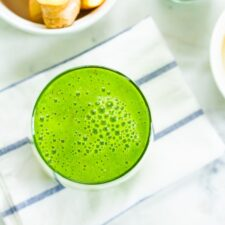 Lime green smoothies on a striped napkin, with bowls of apple slices, ginger, pineapple and chia seeds around the smoothie on a white marble table.
