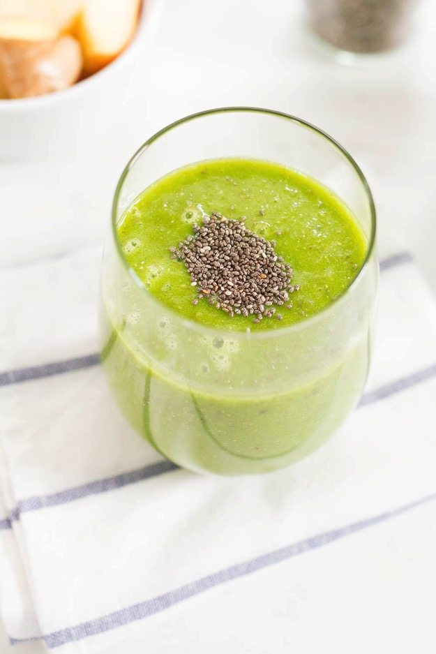 Pineapple recovery smoothie with frozen pineapple, apple, kale, lemon, ginger and chia seeds.