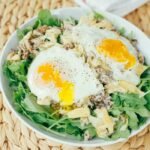 Arugula with artichoke, sardines, and over easy eggs in a white bowl on a wicker mat.