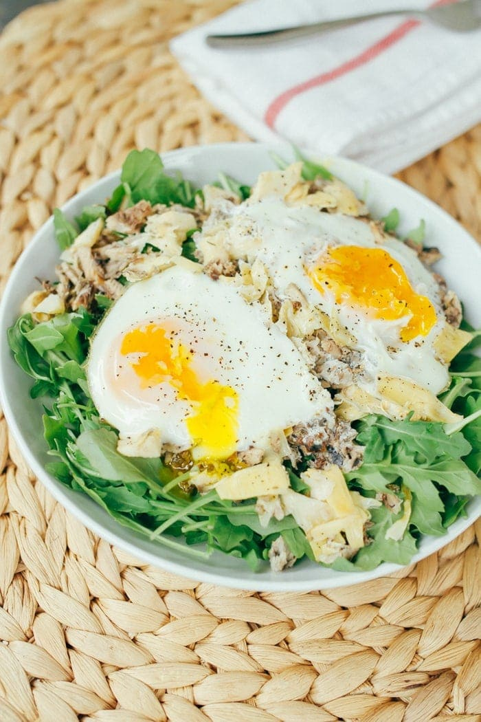 A quick and simple low-carb paleo breakfast salad with sardines, artichokes and eggs, baked and served over fresh arugula.