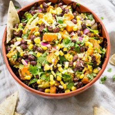 Southwest sweet potato dip with corn beans, sweet potato, cilantro, avocado and purple onion in a bowl. A chip is sitting in the bowl and a few are on the table.